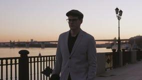 Ένας νεαρός άνδρας σε ένα ελαφριές κοστούμι και μια ΚΑΠ που περπατούν κατά μήκος του περιπάτου το βράδυ απόθεμα βίντεο