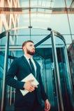 Ένας νεαρός άνδρας σε ένα επιχειρησιακό κοστούμι με μια ταμπλέτα στα χέρια του Στοκ Εικόνες