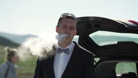 Ένας νεαρός άνδρας σε ένα κλασικό κοστούμι, δεσμός τόξων καπνίζει VAPE Στάσεις δίπλα στο αυτοκίνητο στη φύση φιλμ μικρού μήκους