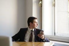 Ένας νεαρός άνδρας σε ένα μαύρο επιχειρησιακό κοστούμι, ένα άσπρους πουκάμισο και έναν δεσμό που μιλούν ήρεμα σε ένα τηλέφωνο κυτ στοκ εικόνες