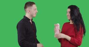 Ένας νεαρός άνδρας σε ένα μαύρο πουκάμισο μεταχειρίζεται ένα ελκυστικό brunette ένα καυτό τσάι από μια θερμο κούπα φιλμ μικρού μήκους