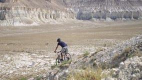 Ένας νεαρός άνδρας σε ένα ποδήλατο κυλά από το βουνό κίνηση αργή φιλμ μικρού μήκους