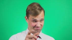 Ένας νεαρός άνδρας σε ένα πουκάμισο και δεσμός σε ένα πράσινο υπόβαθρο Πορτρέτο Συγκινήσεις και χειρονομίες 4k, κινηματογράφηση σ απόθεμα βίντεο