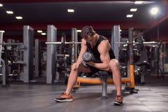 Ένας νεαρός άνδρας, σκοτεινός εξοπλισμός ικανότητας γυμναστικής στο εσωτερικό, ένα χέρι άλαλο Στοκ Φωτογραφία