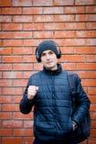Ένας νεαρός άνδρας στέκεται ενάντια σε έναν τουβλότοιχο και ακούει μουσική στα ακουστικά στοκ εικόνα με δικαίωμα ελεύθερης χρήσης
