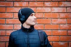 Ένας νεαρός άνδρας στέκεται ενάντια σε έναν τουβλότοιχο και ακούει μουσική στα ακουστικά στοκ εικόνες με δικαίωμα ελεύθερης χρήσης