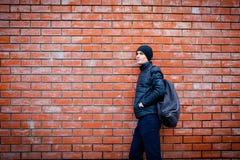 Ένας νεαρός άνδρας στέκεται ενάντια σε έναν τουβλότοιχο περιμένοντας κάτι στοκ φωτογραφίες με δικαίωμα ελεύθερης χρήσης