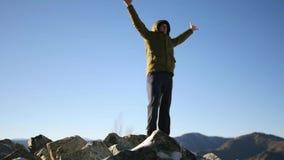 Ένας νεαρός άνδρας στέκεται πάνω από ένα βουνό, απολαμβάνοντας της ελευθερίας και της ομορφιάς γύρω σε αργή κίνηση, 1920x1080, πλ φιλμ μικρού μήκους