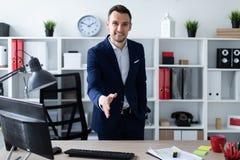 Ένας νεαρός άνδρας στέκεται στο γραφείο κοντά στον πίνακα και επεκτείνει το χέρι του μπροστινό Ο νεαρός άνδρας λέει γειά σου Στοκ φωτογραφία με δικαίωμα ελεύθερης χρήσης