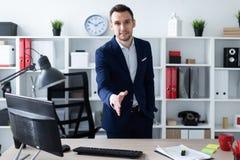 Ένας νεαρός άνδρας στέκεται στο γραφείο κοντά στον πίνακα και επεκτείνει το χέρι του μπροστινό Ο νεαρός άνδρας λέει γειά σου Στοκ Εικόνα