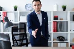 Ένας νεαρός άνδρας στέκεται στο γραφείο κοντά στον πίνακα και επεκτείνει το χέρι του μπροστινό Ο νεαρός άνδρας λέει γειά σου Στοκ Εικόνες