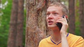 Ένας νεαρός άνδρας στα ξύλα κάθεται κοντά σε ένα δέντρο και μιλά στο τηλέφωνο απόθεμα βίντεο