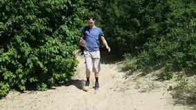 Ένας νεαρός άνδρας στα σορτς και μια μπλούζα τρέχει έξω στην παραλία από το δάσος και εξετάζει το χάρτη Άτομο σε μια βιασύνη απόθεμα βίντεο