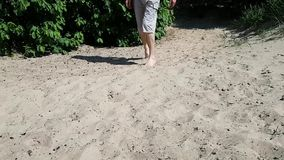 Ένας νεαρός άνδρας στα σορτς περπατά στην άμμο και Η ασθένεια είναι εγκεφαλική παράλυση Χωλότητα στον ενήλικο απόθεμα βίντεο