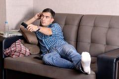 Ένας νεαρός άνδρας στα τζιν, με έναν τηλεχειρισμό για την πλήξη TV στο πρόσωπο αλλάζει το κανάλι Στοκ Εικόνες