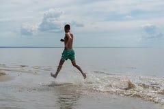Ένας νεαρός άνδρας στα τρεξίματα σορτς κατά μήκος του νερού κατά μήκος της ακτής Στοκ εικόνες με δικαίωμα ελεύθερης χρήσης