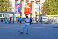 Ένας νεαρός άνδρας στην άσπρα μπλούζα και το τζιν παντελόνι στέκεται στο τετράγωνο για το περπάτημα στο πάρκο με ένα πόδι που τρα στοκ φωτογραφία