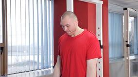Ένας νεαρός άνδρας συμμετέχει στη γυμναστική με ένα barbell Αθλητισμός, δύναμη, υγεία φιλμ μικρού μήκους