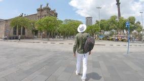 Ένας νεαρός άνδρας, τουρίστας με ένα σακίδιο πλάτης και σε ένα καπέλο που περπατά στο κέντρο της Βαρκελώνης, Ισπανία απόθεμα βίντεο