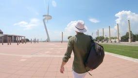 Ένας νεαρός άνδρας, τουρίστας που περπατά με ένα σακίδιο πλάτης και σε ένα καπέλο κοντά στον πύργο επικοινωνίας του Σαντιάγο Cala φιλμ μικρού μήκους