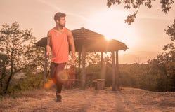Ένας νεαρός άνδρας, τρέξιμο, δρομέας, αθλητικά ενδύματα, υπαίθρια ηλιόλουστη DA Στοκ Εικόνα