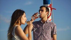 Ένας νεαρός άνδρας φλερτάρει με μια γυναίκα που έχει ένα γυαλί του οινοπνεύματος στο χέρι του απόθεμα βίντεο