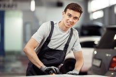 Ένας νεαρός άνδρας χαμογελά γυαλίζοντας ένα αυτοκίνητο σε μια συντήρηση οχημάτων στοκ εικόνα