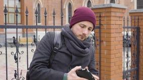 Ένας νεαρός άνδρας χρησιμοποιεί μια ταμπλέτα στην πόλη απέναντι από την εκκλησία φιλμ μικρού μήκους