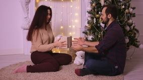 Ένας νεαρός άνδρας δίνει τη φίλη του για τα Χριστούγεννα Οι εραστές κάθονται μπροστά από την εστία στον μπεζ τάπητα απόθεμα βίντεο