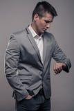 Ένας νεαρός άνδρας, ανώτερο σώμα, επίσημα ενδύματα, που κοιτάζει στο ρολόι Στοκ Εικόνα