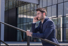 Ένας νεαρός άνδρας, δεσμός κοστουμιών, που μιλά πέρα από το τηλέφωνο, υπαίθρια ημέρα, moder Στοκ Εικόνες