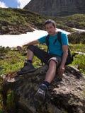 Ένας νεαρός άνδρας κάθεται σε έναν βράχο και μια εκμετάλλευση ένα μαχαίρι πετρών Στοκ εικόνες με δικαίωμα ελεύθερης χρήσης