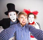 Ένας νεαρός άνδρας και ένα αστείο ζεύγος των mimes που παίρνουν μια φωτογραφία selfie στοκ φωτογραφία