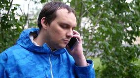 Ένας νεαρός άνδρας με ένα τηλέφωνο στο αυτί του, ακούει αυτό που έχει την υποχρέωση για κίνηση αργή 1920x1080 Πλήρες HD απόθεμα βίντεο