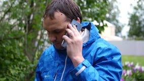 Ένας νεαρός άνδρας με ένα τηλέφωνο στο αυτί του, ακούει προσεκτικά αυτό που έχει την υποχρέωση για κίνηση αργή 1920x1080 Πλήρες H απόθεμα βίντεο