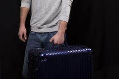 Ένας νεαρός άνδρας με μια μεγάλη μπλε βαλίτσα Στοκ Φωτογραφίες