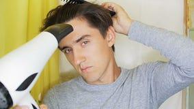 Ένας νεαρός άνδρας ξεραίνει την τρίχα του με έναν στεγνωτήρα τρίχας απόθεμα βίντεο