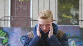 Ένας νεαρός άνδρας που πάσχει από τον πονοκέφαλο και έπειτα που χαμογελά φιλμ μικρού μήκους