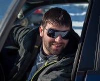 Ένας νεαρός άνδρας που φορά τα γυαλιά ηλίου σε ένα ιδιωτικό αυτοκίνητο Στοκ Εικόνες