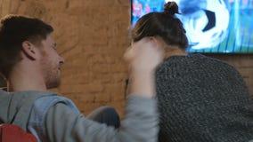 Ένας νεαρός άνδρας προσέχει το ποδόσφαιρο στη TV με τη φίλη του απόθεμα βίντεο