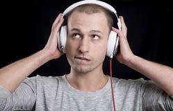 Ένας νεαρός άνδρας σε μια γκρίζα μπλούζα που ακούει τη μουσική στα ακουστικά Στοκ εικόνα με δικαίωμα ελεύθερης χρήσης
