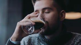 Ένας νεαρός άνδρας σε μια θερμή μπύρα ξανθού γερμανικού ζύού πουλόβερ χύνοντας στο γυαλί και τα ποτά αυτό με την ευχαρίστηση, είν απόθεμα βίντεο