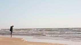 Ένας νεαρός άνδρας στέκεται σε μια όμορφη αμμώδη παραλία που ενυδατώνει τα πόδια του στη θάλασσα εξετάζοντας τα κύματα που καλύπτ απόθεμα βίντεο
