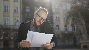 Ένας νεαρός άνδρας στα γυαλιά του κρατά τα έγγραφα στο χέρι του απόθεμα βίντεο