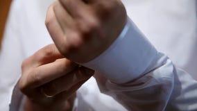 Ένας νεόνυμφος που βάζει στα μανικετόκουμπα καθώς παίρνει ντυμένος στην επίσημη ένδυση κοστούμι νεόνυμφων s φιλμ μικρού μήκους