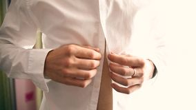 Ένας νεόνυμφος που βάζει στα μανικετόκουμπα καθώς παίρνει ντυμένος στην επίσημη ένδυση φιλμ μικρού μήκους