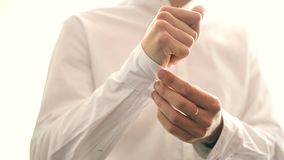 Ένας νεόνυμφος που βάζει στα μανικετόκουμπα καθώς παίρνει ντυμένος στην επίσημη ένδυση απόθεμα βίντεο