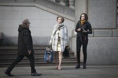 Ένας ξανθός σε ένα χρυσό φόρεμα και έναν γκρίζο επενδύτη κατεβαίνει τα σκαλοπάτια Στοκ Εικόνες