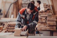 Ένας ξυλουργός απασχολείται στην ξυλουργική στην εργαλειομηχανή Ξυλουργός που εργάζεται στις μηχανές ξυλουργικής στο κατάστημα ξυ Στοκ φωτογραφία με δικαίωμα ελεύθερης χρήσης
