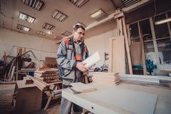 Ένας ξυλουργός απασχολείται στην ξυλουργική στην εργαλειομηχανή Ξυλουργός που εργάζεται στις μηχανές ξυλουργικής στο κατάστημα ξυ Στοκ Φωτογραφία